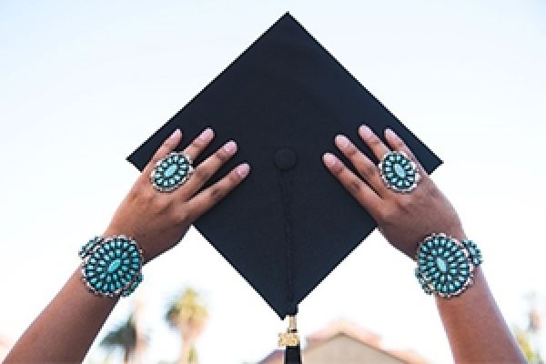 Native American wearing turquoise rings and bracelets, holding up graduation cap