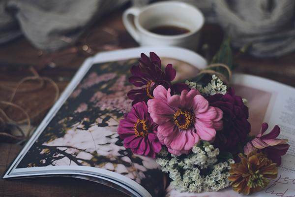 coffee, a book and flowers on a table