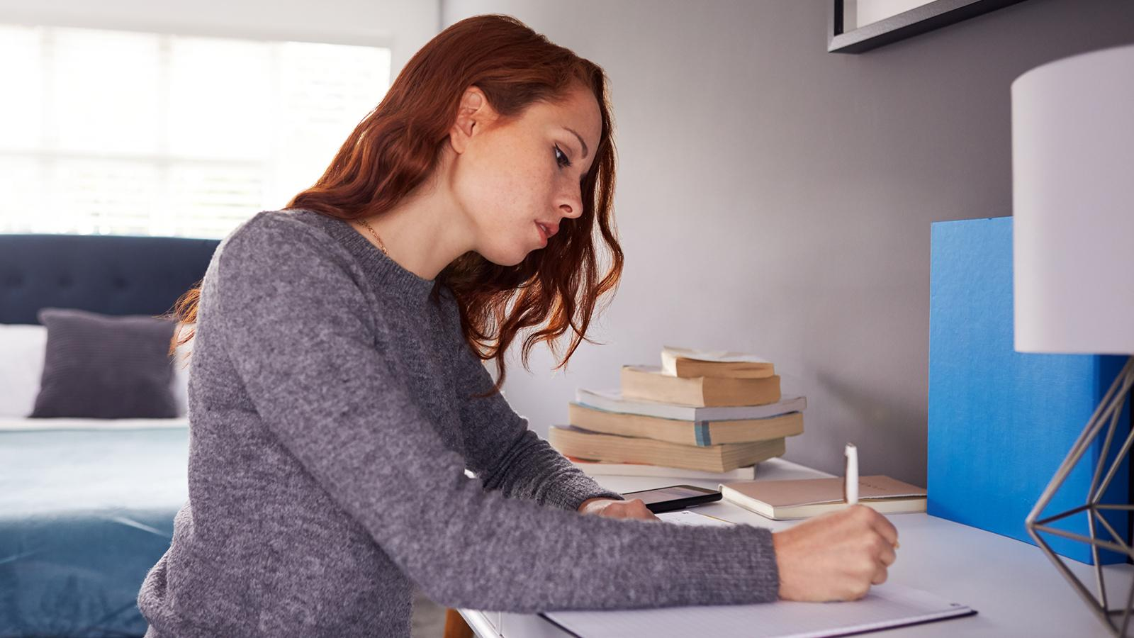 female college student working on a paper